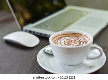 Laptop with coffee cup on wood table