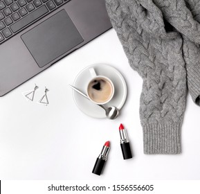 Laptop, coffee cup, sweater, lipsticks and glasses. Stylish office desk. Autumn or Winter feminine concept. Flat lay, top view