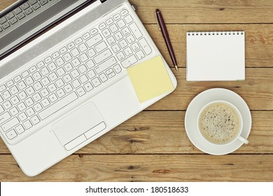 laptop, coffee and notepad on wooden surface