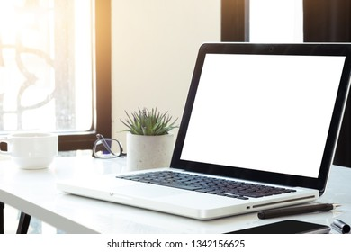 Laptop computer with blank mock up screen is on top white office desk table with cup of coffee and supplies.