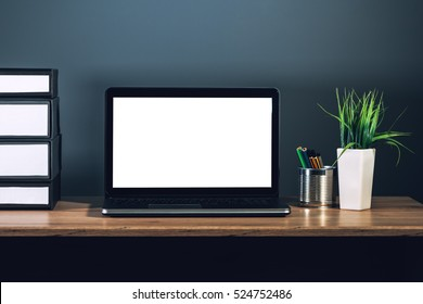 Laptop computer with blank screen as copy space placed on office desktop in dark interior.