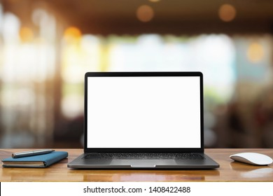 laptop computer blank white screen and pen on table in cafe background