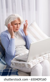 Laptop computer broke in elderly woman. Frustrated lady looking disappointed by new computer technologies.