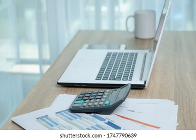 Laptop computer and calculator and coffee cup and business document on the working desk.
