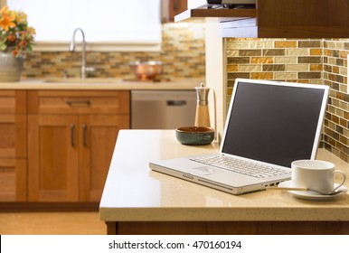 Laptop computer in contemporary upscale home kitchen interior with cherry wood cabinets, quartz countertops and glass tile mosaic backsplash. Selective focus on laptop.