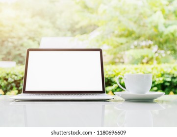 Laptop computer and cup of coffee on the table outdoor in morning with blurred green plant background