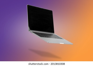 Laptop  computer with empty screen while levitating in the air on a background illuminated by a purple and orange color gradient. Creative minimal background. Pop art, conceptual art.