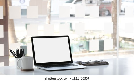 Laptop computer with mockup or blank screen on white desk in workspace and copy space concept