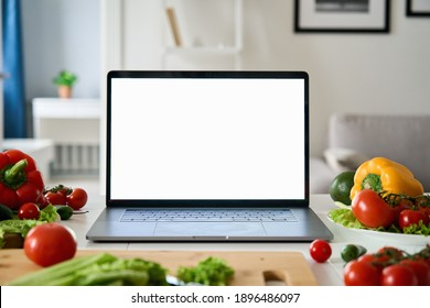 Laptop computer with mockup white screen on vegetarian healthy food vegetable background. Online grocery shopping delivery app ads concept, cook book diet plan nutrition recipes, close up view.
