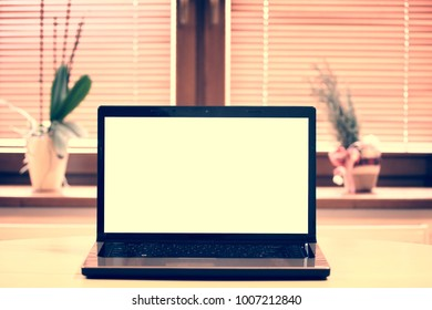 Laptop computer on table in home on window background.
