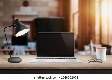 Laptop computer on table in office with brick walls. Window and sunlight in background.