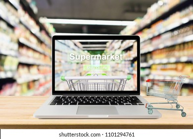 laptop computer on wood table with supermarket aisle blurred background online shopping concept