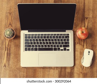 Laptop computer on Wooden Background with Apple Fruit and Cactus Flower. Work place at home