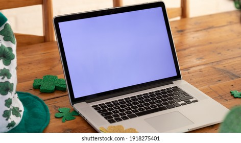 Laptop computer on a wooden dining table with shamrock decorations for st patrick's day. . Staying at home in self isolation during quarantine lockdown. - Shutterstock ID 1918275401