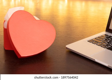 Laptop computer and an open heart-shaped gift box on a dark wooden table against a background of lights. Online shopping and chatting, virtual Valentine's Day, love in time COVID-19 concept.