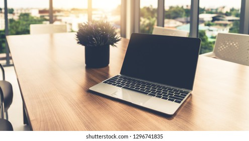 Laptop computer with opened lid on table in office workspace.