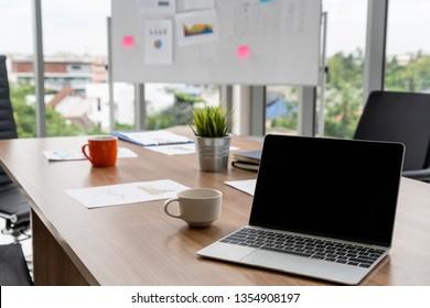 Ordinateur portable avec couvercle ouvert sur la table dans la salle de réunion de l'espace de travail de bureau.