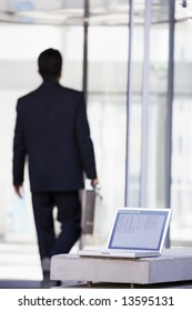 Laptop computer outside office with businessman in background