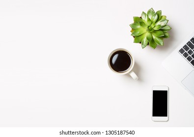 Laptop computer with plant in a pot, cup of coffee and modern mobile phone on white background. Conceptual workspace or business concept. Free space for your text