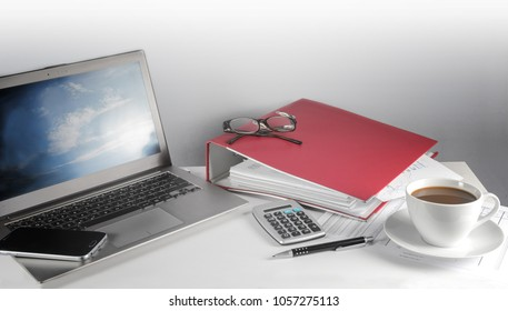 laptop computer, red folder, calculator and a cup of coffee on a office desk, finance and business concept with copy space, wide format, selected focus, narrow depth of field