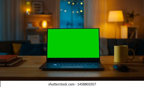 Laptop Computer Showing Green Key Screen Stands on a Desk in the Living Room. In the Background Cozy Living Room in the Evening with Warm Lights on.