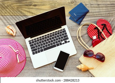 Laptop computer and smart phone with beach accessories on wooden board