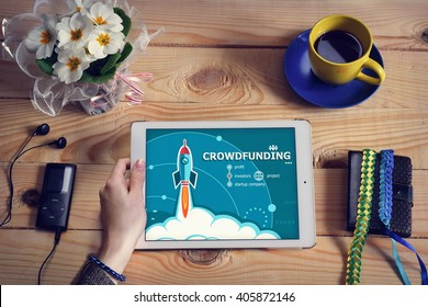 Laptop computer, tablet pc and Crowdfunding design concept on wooden office desk with copy space. Crowdfunding design concept background with rocket.