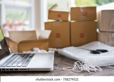 laptop computer at workplace of start up, small business owner. cardboard parcel box of product for deliver to customer.  Online selling, e-commerce, packing concept