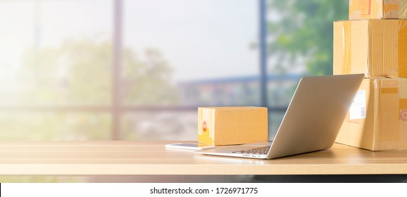 Laptop computer at workplace of start up,small business owner. cardboard parcel box of product for deliver to customer.Online selling, e-commerce,packing concept,Morning light,work from home,