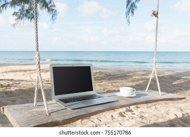 Laptop and a cup of coffee sea view backdrop.copy space. Selected focus  computer laptop with coffee mug on swing cradle under tree. makeshift cradle