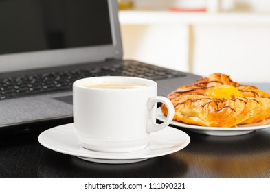 laptop and cup of hot evaporating coffee on table