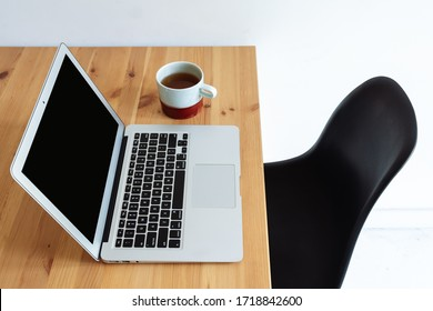 Laptop with a cup of tea on a wooden table and a black chair