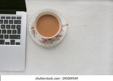 Laptop and cup of tea in a vintage cup and saucer. On a white distressed table top.