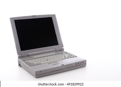 Laptop dating from the 90's, with a port door open, on a white background