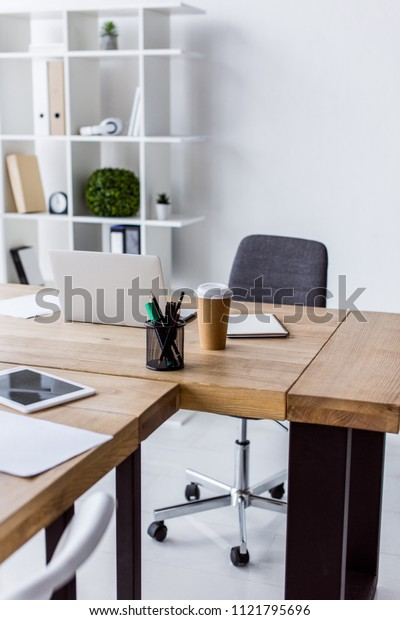 laptop and disposable coffee cup on table in business office