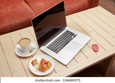 Laptop e banking token croissant and coffe on cafe's table