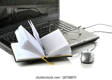 laptop with exchange diagram, organizer, glasses on white