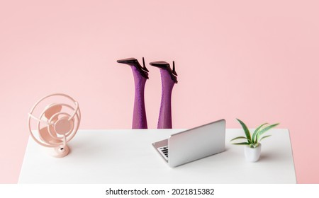 laptop and a fan on the table next to female legs sticking out from under the table