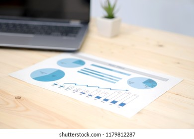 laptop and financial graph on white paper on working table