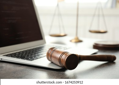 Laptop, gavel and scales on table, closeup. Cyber crime