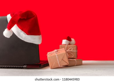 Laptop and gifts on the table with Santa Claus hat on a red background, holiday concept and preparation for Christmas