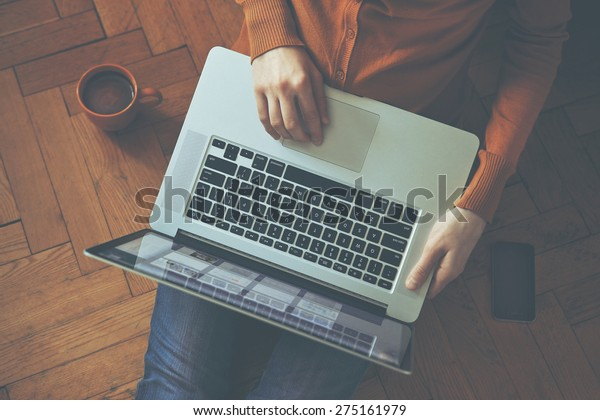 Laptop in girl's hands sitting on a wooden floor