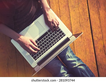 Laptop in girls hands typing and sitting on a wooden floor