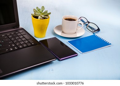 Laptop, glasses, coffee and plant on a blue wooden table