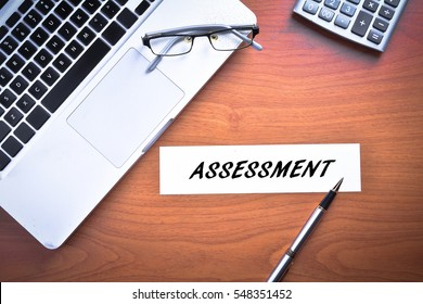 Laptop with glasses, pen and calculator with text ASSESSMENT