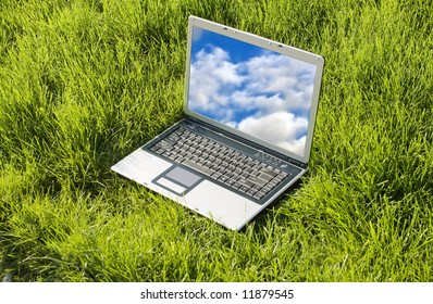 laptop in the grass with cloudy sky on display,working in nature, aiming high , free communication