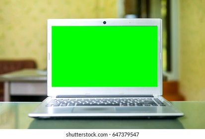 Laptop with Green screen on table. coffee shop blurred background.