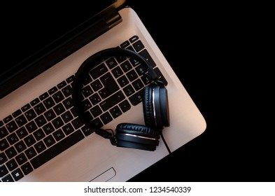 Laptop with headphones isolated on a black background