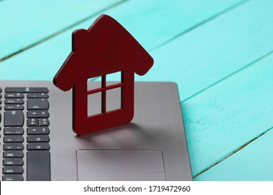 Laptop with house figure on a blue wooden background. Online rental reservation