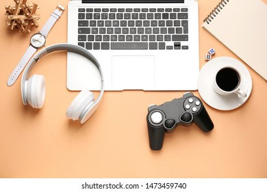 Laptop with joypad, headphones and cup of coffee on color background